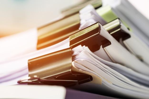 Unvollendete dokumentenstapel von aktenordnern auf dem schreibtisch für berichtspapiere, stapel von blättern