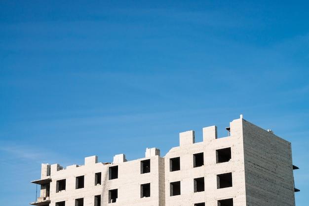 Unvollendetes backsteingebäude mit mehreren wohnungen aus weißem backstein auf dem hintergrund des blauen himmels. bauen sie häuser aus der nähe. industrie bauen. minimalistisch.