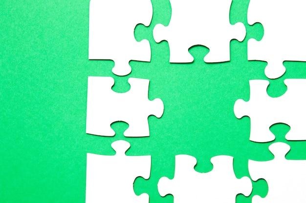 Unvollendetes puzzle aus weißem karton auf grünem hintergrund und ein ungeeignetes teil eines anderen puzzles, ein teil fehlt, kopierraum, suche nach einem geeigneten teil