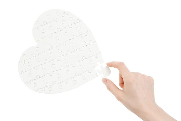 Unvollständiges puzzle in form eines herzens isoliert auf weiß