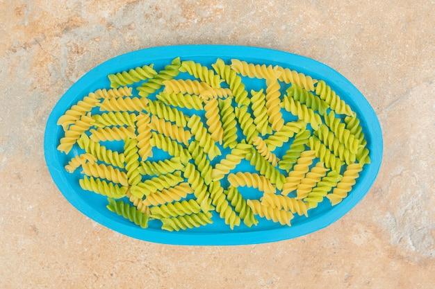 Unvorbereitete spiralmakkaroni auf blauem teller