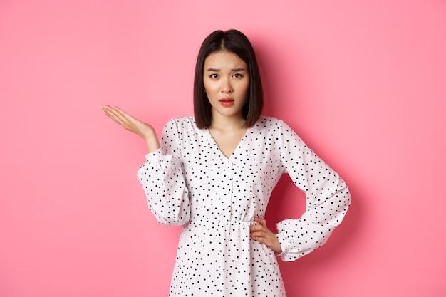 Unvorsichtige asiatische frau, die die hand hebt und die achseln zuckt, unbehelligt und befragt in die kamera starrt, also welche geste, die auf rosa hintergrund steht?