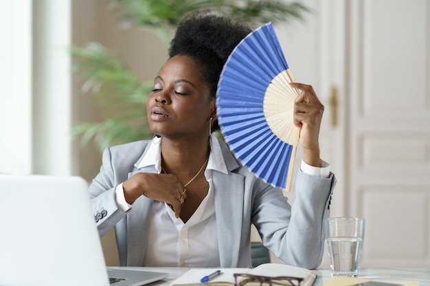 Unwohle afrikanische geschäftsfrau-büroangestellte erleiden einen hitzschlag am arbeitsplatz ohne klimaanlage