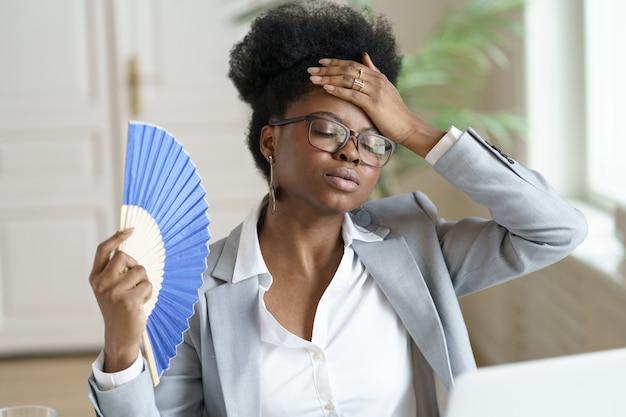 Unwohle schwarze geschäftsfrau, die schwankt, fühlt sich krank, heiß und überhitzt bei der arbeit am computer im heimbüro