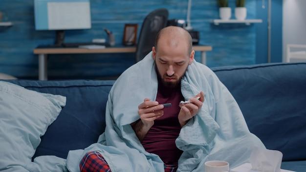 Unwohler mann, der tabletten mit kapseln in der hand hält
