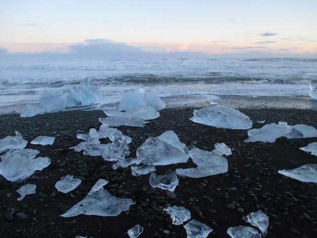 Unzählbare eisberge auf dem schwarzen sandstrand gegen sonnenunterganghimmel, südisland