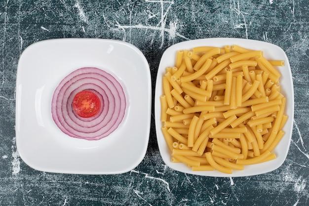 Unzubereitete frische makkaroni mit zwiebelscheiben und tomatenkirsche.