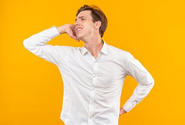 Unzufrieden aussehender junger gutaussehender kerl mit weißem hemd, der die hände mit der hüfte auf die wange legt