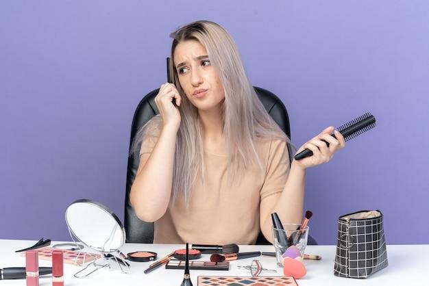 Unzufrieden aussehendes junges schönes mädchen sitzt am tisch mit make-up-tools, die haare auf blauem hintergrund kämmen
