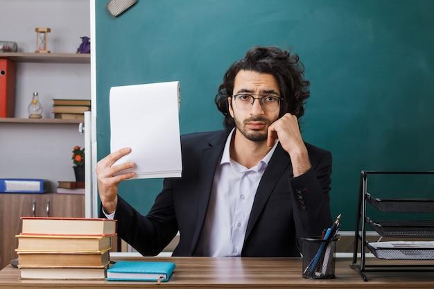 Unzufrieden, die hand auf die wange zu legen männlicher lehrer mit brille, der papier hält, das am tisch mit schulwerkzeugen im klassenzimmer sitzt