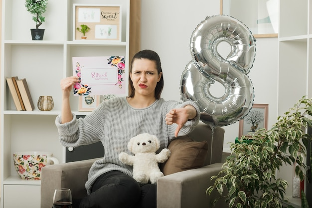 Unzufrieden mit daumen nach unten schönes mädchen am glücklichen frauentag mit grußkarte auf sessel im wohnzimmer sitzend