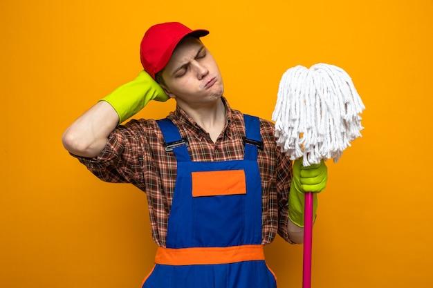 Unzufrieden mit geschlossenen augen, die hand auf den hals legen, junger reinigungsmann in uniform und mütze mit handschuhen, die mop halten