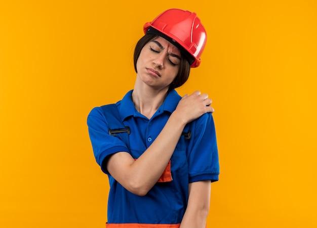 Unzufrieden mit geschlossenen augen junge baumeisterin in uniform, die hand auf die schulter legt, isoliert auf gelber wand