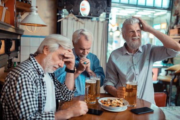 Unzufrieden nach dem anschauen. drei rentner sind unzufrieden, nachdem sie in der kneipe fußball geschaut haben