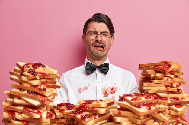 Unzufrieden weinender mann hat schmutziges weißes hemd als brot snack nicht sorgfältig gegessen, drückt negative gefühle aus, trägt elegante kleidung, hat unglücklichen tag, besucht café oder restaurant, isoliert auf rosa wand