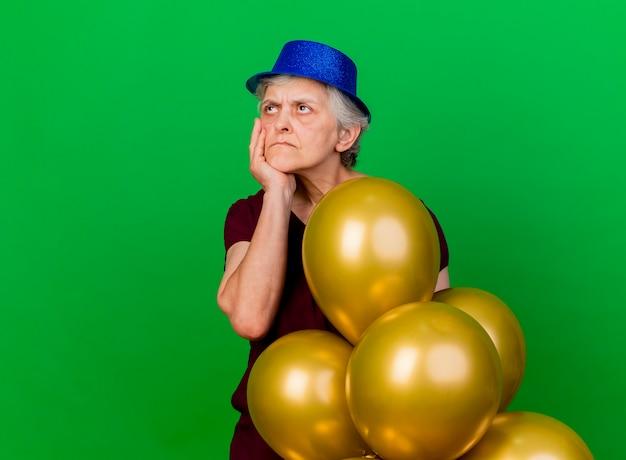 Unzufriedene ältere frau, die partyhut trägt, setzt hand auf kinn, das mit heliumballons steht und seite auf grün betrachtet