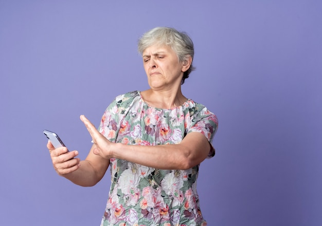 Unzufriedene ältere frau hält und gibt vor, telefon isoliert auf lila wand zu schieben
