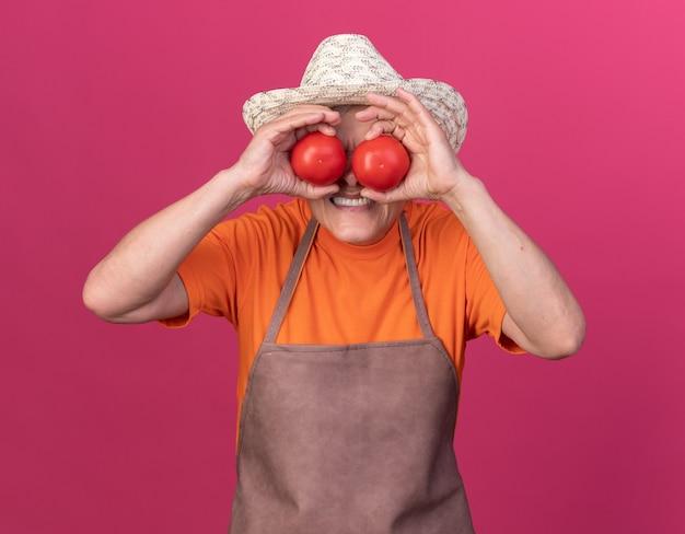 Unzufriedene ältere gärtnerin mit gartenhut, die die augen mit tomaten bedeckt