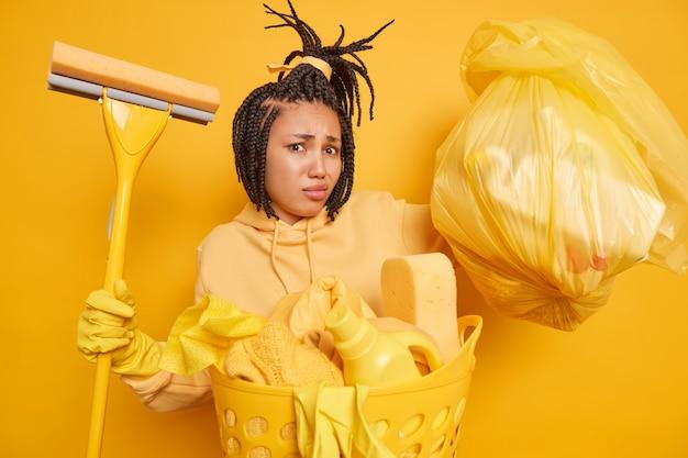 Unzufriedene afroamerikanerin hat dreadlocks, die damit beschäftigt sind, hausarbeit zu machen, hält tasche mit reinigungsmitteln