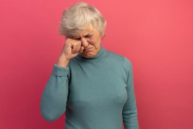 Unzufriedene alte frau mit blauem rollkragenpullover und sonnenbrille, die das auge mit geschlossenen augen abwischt, isoliert auf rosafarbener wand mit kopierraum