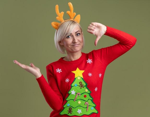 Unzufriedene blonde frau mittleren alters, die weihnachtsrentiergeweih-stirnband und weihnachtspullover trägt, die kamera betrachten daumen unten und leere hand lokalisiert auf olivgrünem hintergrund