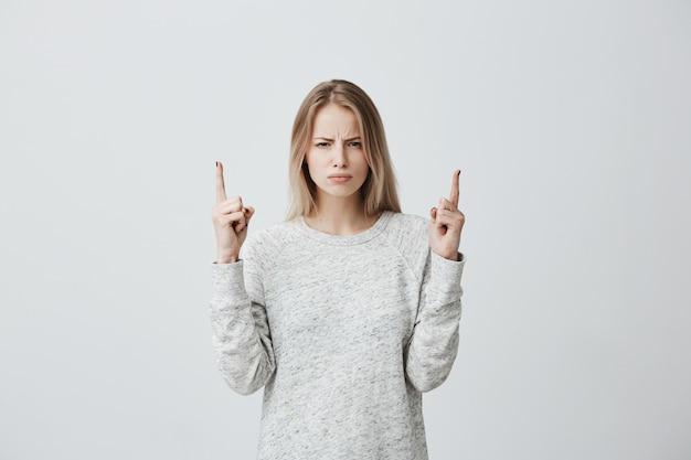 Unzufriedene blonde frau runzelt die stirn, schaut wütend und zeigt mit den fingern auf den kopierraum über dem kopf