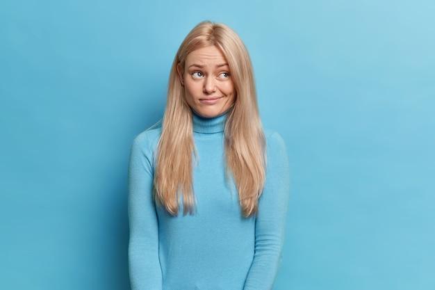 Unzufriedene blonde junge frau mit langen haaren sieht verärgert beiseite hat nachdenklichen ausdruck geldbörsen lippen trägt rollkragenpullover