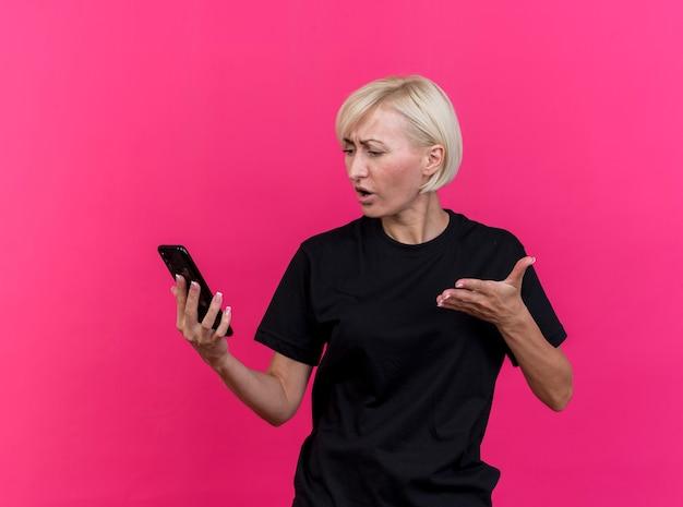 Unzufriedene blonde slawische frau mittleren alters, die handy hält und betrachtet, das hand in der luft lokalisiert auf purpurrotem hintergrund hält