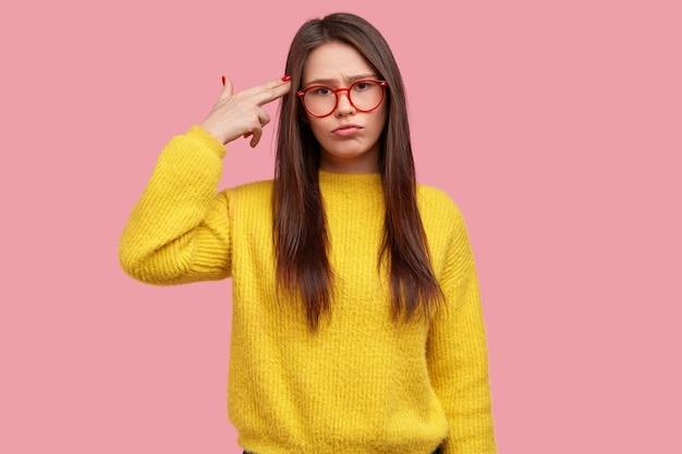 Unzufriedene brünette dame macht selbstmordgeste, erschießt sich in der schläfe, fühlt sich der arbeit müde, trägt eine brille und einen gelben pullover