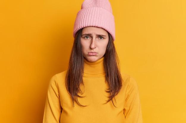Unzufriedene brünette junge frau hat beleidigten ausdruck mürrischer blick drückt negative emotionen aus trägt hut und lässigen pullover.