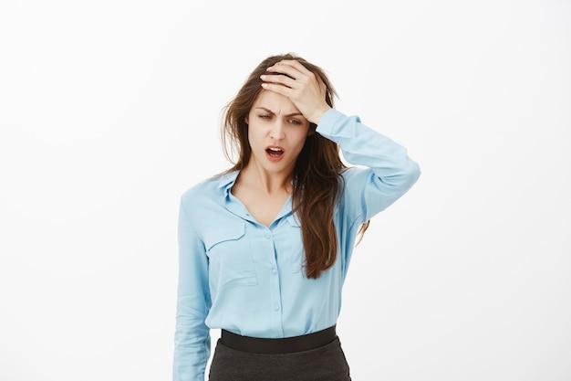 Unzufriedene düstere brünette geschäftsfrau posiert im studio