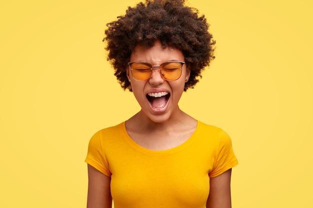 Unzufriedene dunkelhäutige emotionale afroamerikanerin schreit laut, öffnet den mund