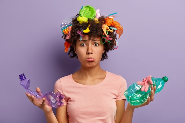 Unzufriedene dunkelhäutige frau kümmert sich um saubere umwelt, hält zwei zerknitterte plastikflaschen, sammelt überall müll, ist traurig wegen naturverschmutzungsproblemen, kümmert sich um ökologie