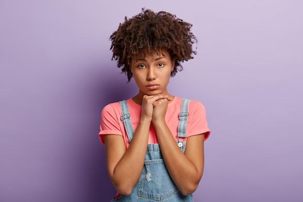 Unzufriedene dunkelhäutige frau mit lockigem haar, hält hände unter dem kinn, fühlt sich einsam und niedergeschlagen nach streit mit freund, hat afro-frisur, trägt lässiges t-shirt isoliert auf lila