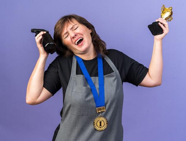 Unzufriedene erwachsene friseurin in uniform mit goldener medaille um den hals, die sprühflasche und siegerpokal isoliert auf lila wand mit kopierraum hält