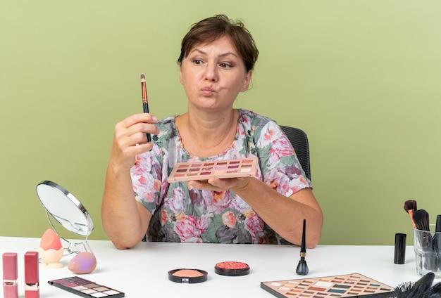 Unzufriedene erwachsene kaukasische frau, die am tisch mit make-up-tools sitzt und lidschatten-palette hält und make-up-pinsel einzeln auf olivgrüner wand mit kopienraum betrachtet
