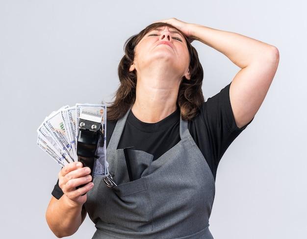 Unzufriedene erwachsene kaukasische friseurin in uniform, die die hand auf die stirn legt und geld mit der haarschneidemaschine hält, die auf weißem hintergrund mit kopienraum isoliert ist