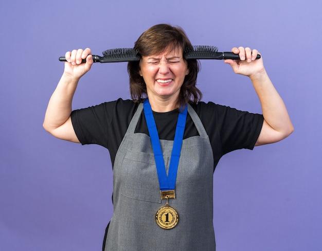 Unzufriedene erwachsene weibliche friseurin in uniform mit goldener medaille um den hals, die mit geschlossenen augen steht und kämme hält, die auf lila wand mit kopienraum isoliert sind