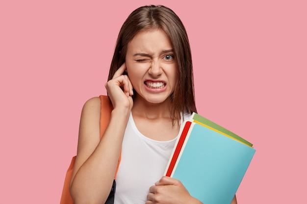 Unzufriedene europäische frau, die sich über unangenehme geräusche ärgert, das ohr verstopft, die zähne mit negativität zusammenbeißt, sich irritiert fühlt