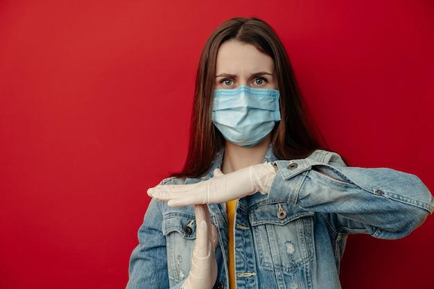 Unzufriedene frau in medizinischen sterilen gesichtsmaskenhandschuhen, zeigt timeout-geste, braucht stopp, isoliert auf roter wand. epidemie pandemische ausbreitung coronavirus 2019-ncov sars covid-19 grippevirus konzept