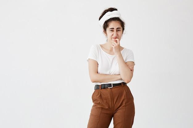 Unzufriedene frau in weißem t-shirt und lappen hat empörten ausdruck, runzelt die augenbrauen, kann etwas nicht verstehen, isoliert gegen weiße wand. unzufriedenes weibliches model hält hand am kinn