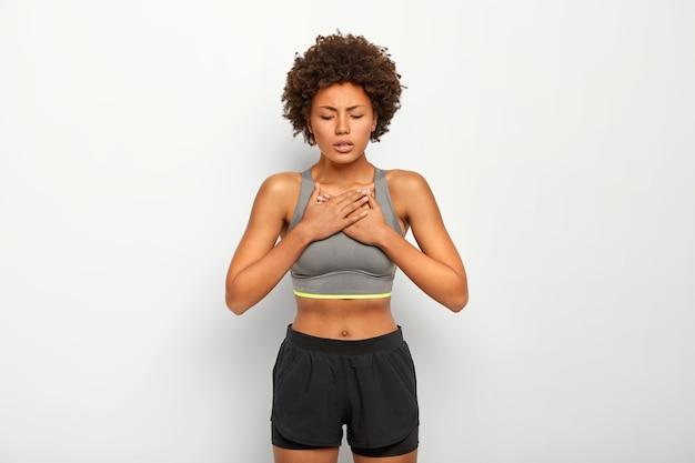Unzufriedene frau leidet an asthmatischem anfall, atmet tief durch, hat atemnot oder atemnot, trägt graues oberteil und shorts