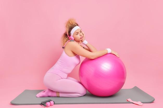 Unzufriedene frau mit lockigen haaren fühlt sich müde, nachdem sich das fitnesstraining auf den schweizer ball stützt