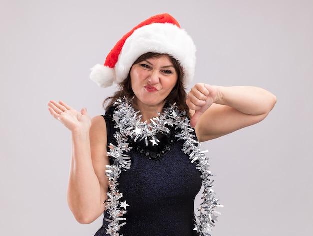 Unzufriedene frau mittleren alters mit weihnachtsmütze und lametta-girlande um den hals, die in die kamera schaut, die leere hand und daumen nach unten isoliert auf weißem hintergrund zeigt