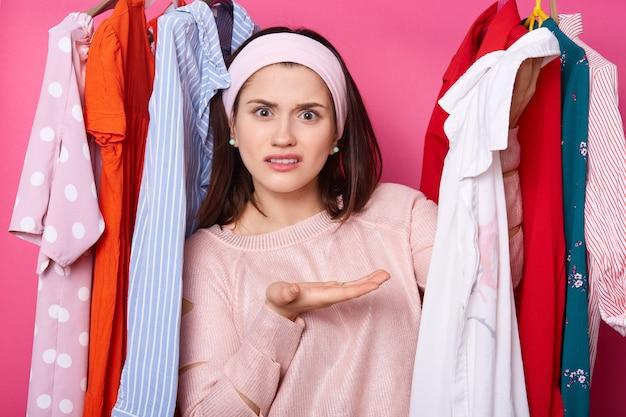 Unzufriedene frau zeigt weißes hemd, unzufrieden mit der größe. mädchen steht an kleidern auf kleiderbügeln im kleiderschrank. unzufriedene dame will die gleiche bluse in verschiedenen farben. einkaufs- und modekonzept.