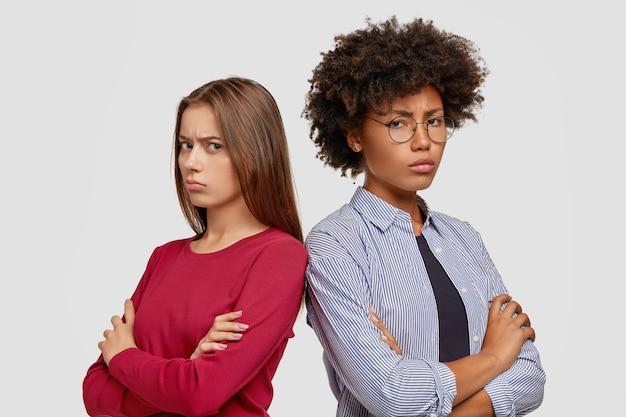 Unzufriedene freundinnen posieren gegen die weiße wand
