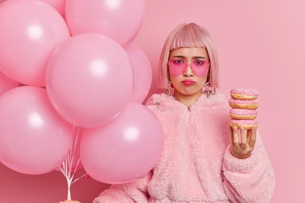 Unzufriedene frustrierte asiatin trägt trendige sonnenbrillen hat schlechte laune, da allein der geburtstag einen haufen donuts und aufgeblasene luftballons hält