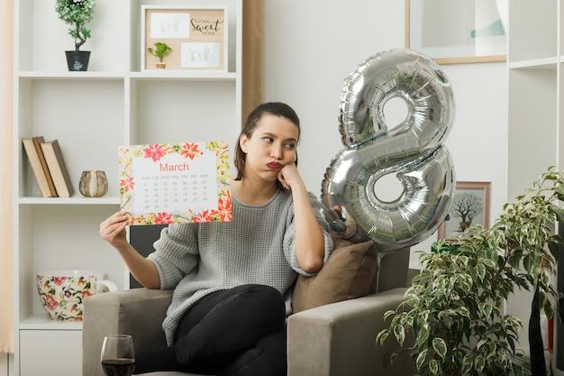 Unzufriedene, geschwollene wangen, die ein schönes mädchen am glücklichen frauentag aussehen, der den kalender hält, der auf einem sessel im wohnzimmer sitzt