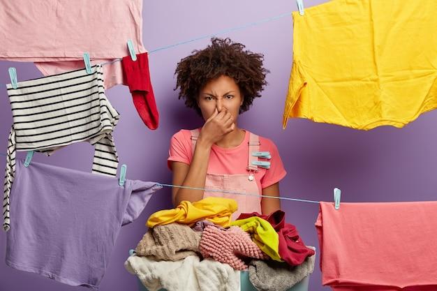 Unzufriedene hausfrau bedeckt nase vor gestank, hält becken mit schmutziger wäsche