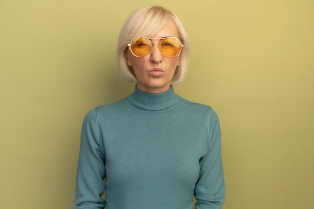 Unzufriedene hübsche blonde slawische frau in der sonnenbrille, die kamera auf olivgrün betrachtet